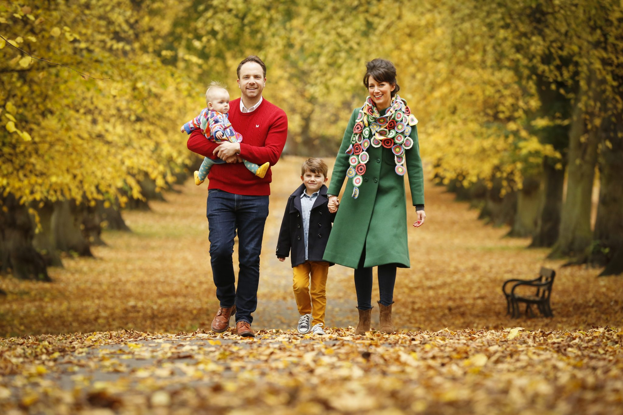 family walking through autumn leaves