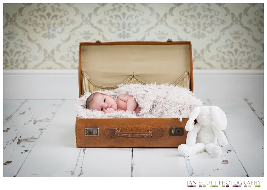 newborn snuggled in a suitcase