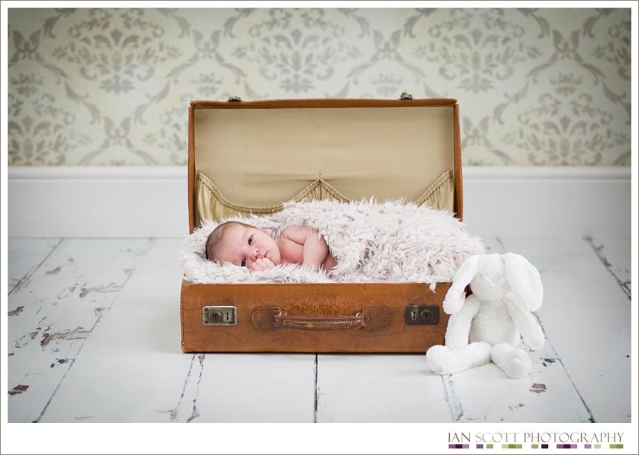 newborn snuggled in a suitcase