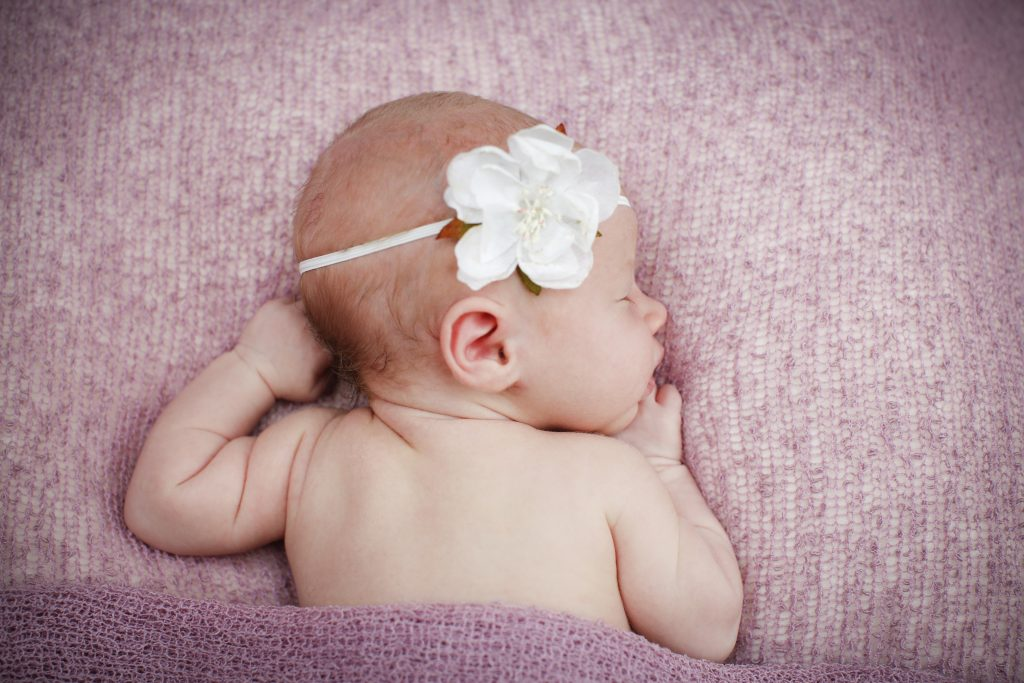 newborn baby girl sleeping on pink blanket with flower headband