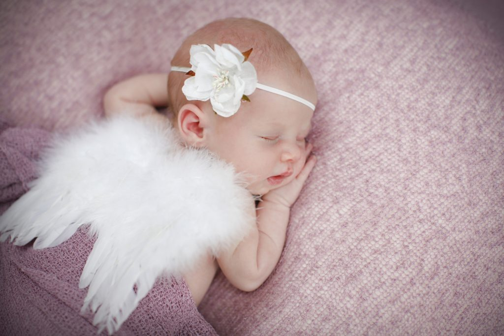 newborn baby girl sleeping on pink blanket with angel wings